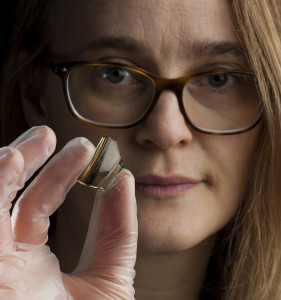 Ingrid Ystgaard, an archaeologist at the NTNU University Museum and project manager for the archaeological survey at the Orland fighter base, holds a shard of a glass beaker imported from the Rhine area in today's Germany. These glass beakers were of great value and show that the farm was relatively well off, with access to products from the continent. Photo: Åge Hojem, NTNU