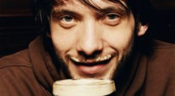 Young Man Enjoying a Drink of Stout in a Pub