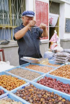 Man selling nuts and dried fruit in Dunhuang, China