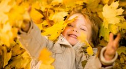 Little child lying in ground and catching falling leaves in autumn