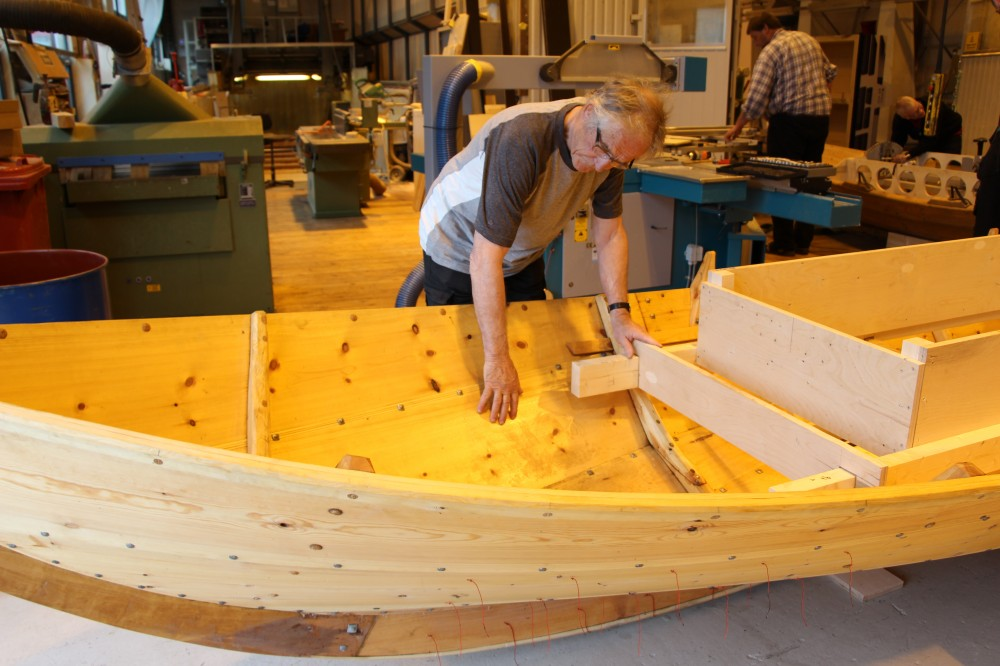 """Jon Bojer Godal examines the hull planks, or strakes, of a geit boat, which translates literally as """"goat boat"""". Photo: N. Bazilchuk"""