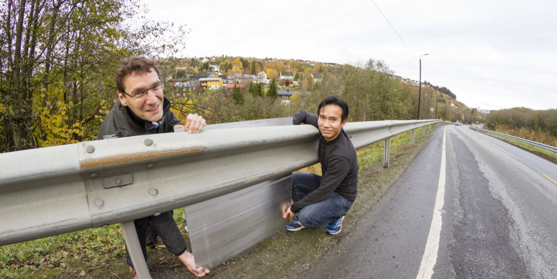 Two men show how a noise barrier will look when integrated in guardrails.