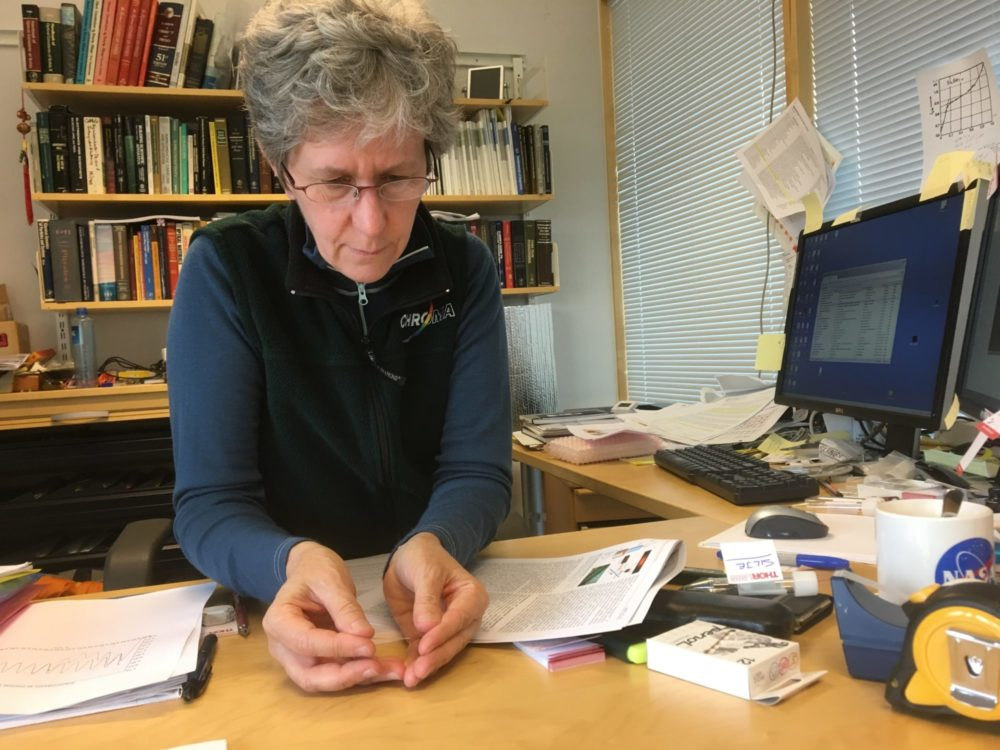 Ursula Gibson, a professor of physics at the Norwegian University of Science and Technology, holds a tiny glass fibre in her hand. A new approach could enhance its performance. Photo: Nancy Bazilchuk, NTNU