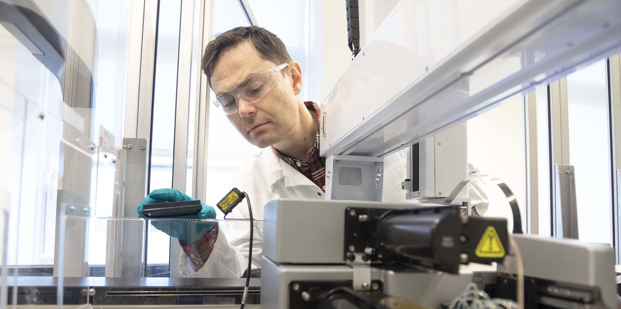 Researcher and biochemist Torkild Visnes in his lab at SINTEF. He is currently working to establish a similar biomedical research group focusing on drug development at SINTEF. Here pictured in front of a biological screening device. Photo: SINTEF/Thor Nielsen.