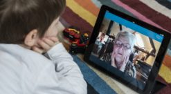 A child videochats with an older woman on a tablet