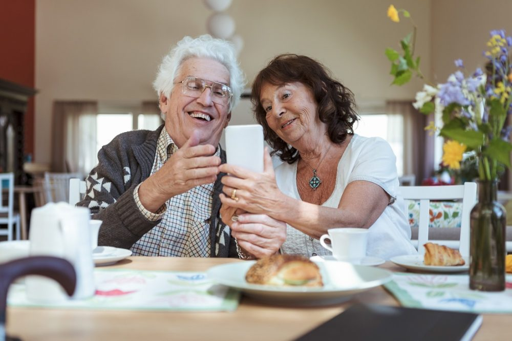 Senior couple taking selfie using mobile phone during breakfast at nursing home