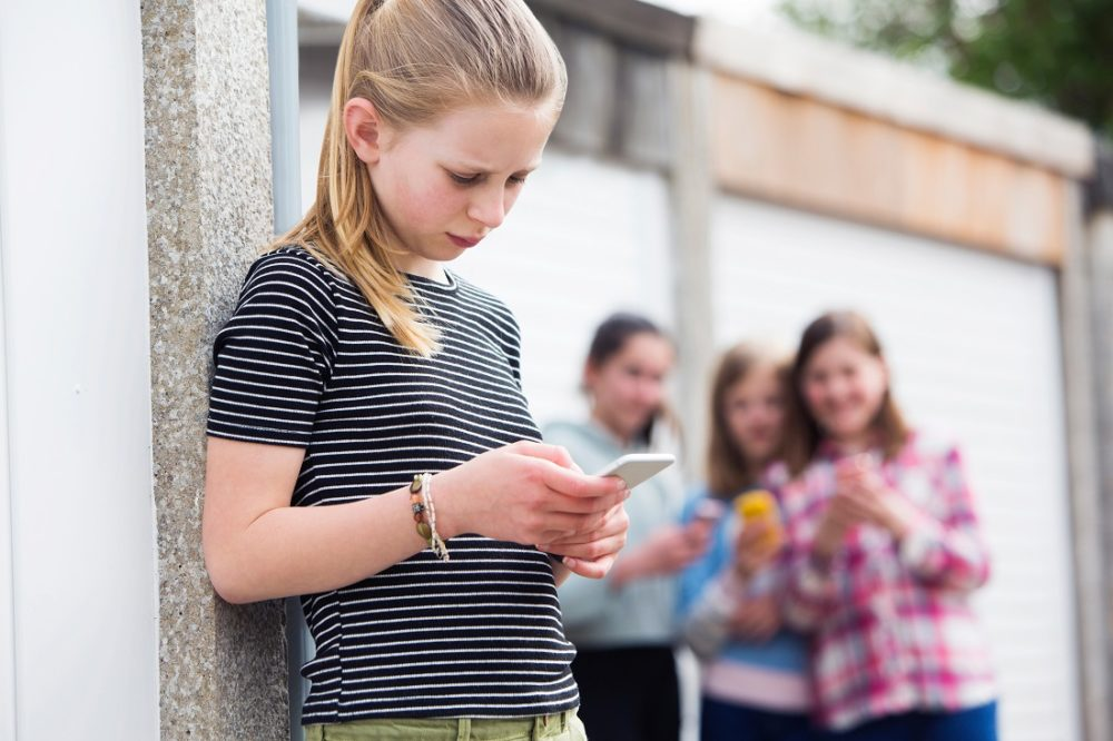 A young girl looks worriedly at her phone as some other girls look at her in the background