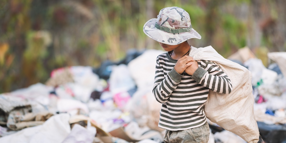 A child carrying a bag past a landfill