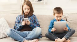 Two children playing video games on a couch