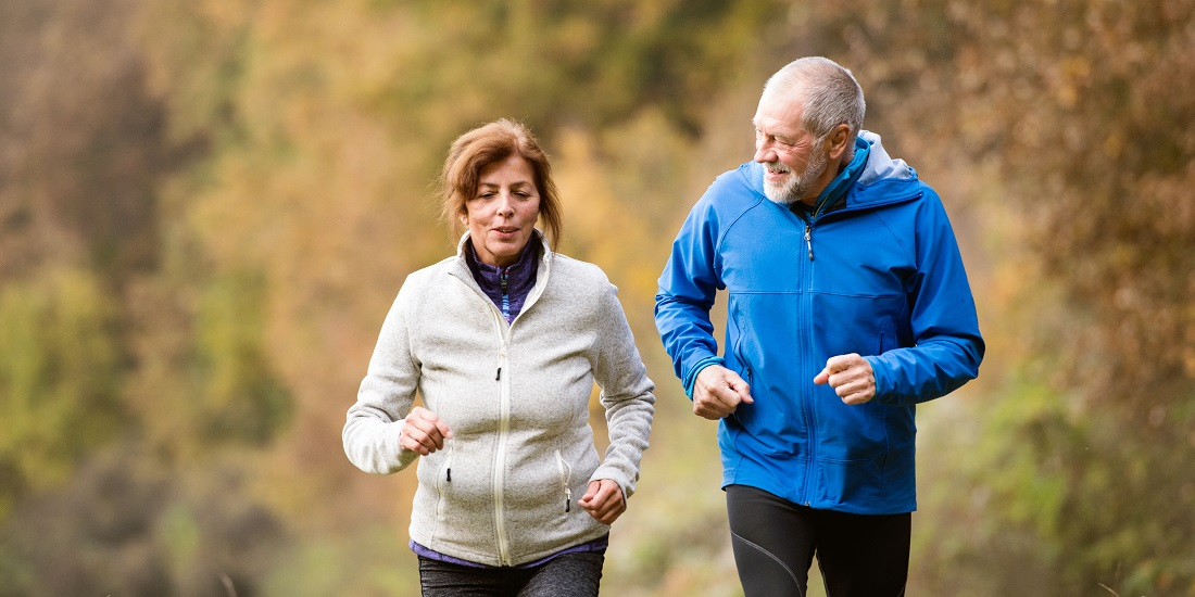 An elderly couple jogging outside