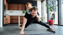 A man doing push-ups with a child on his back