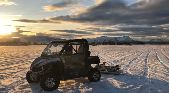 A tiny car with georadar equipment hanging of the back on a snowy field