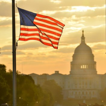 an american flag in front of the capitol building
