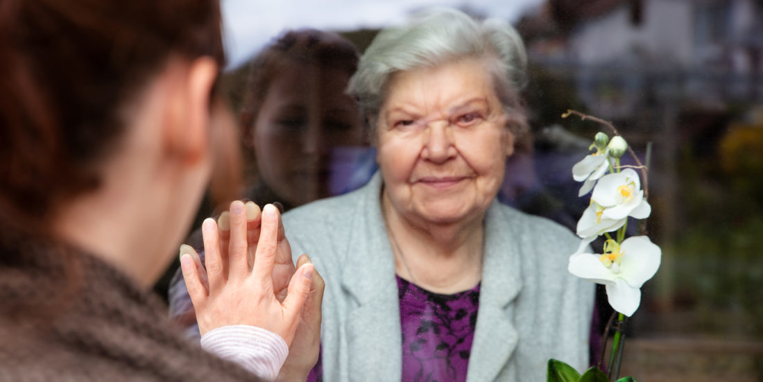 A young man greetings an old woman through a glass window. Both holding their hands on the window from opposite sides
