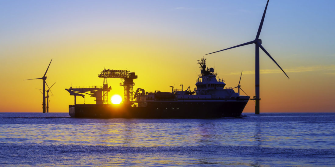 Offshore wind turbines and ship in silhouette in front of beautiful sunset.