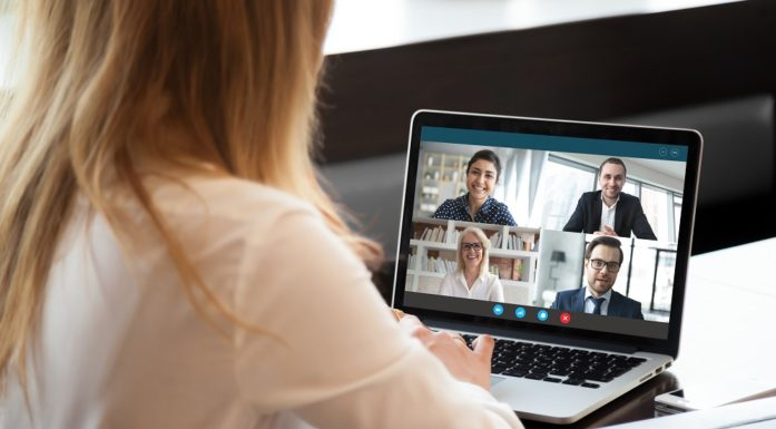 A woman in a digital meeting on a laptop